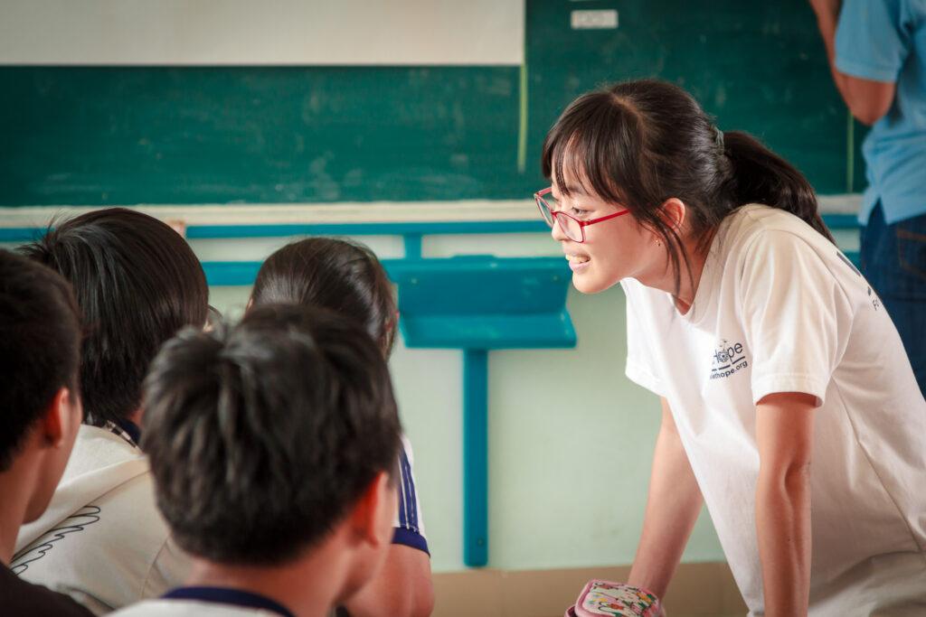 Volunteer working with students.
